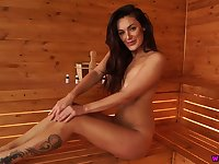 Svelte tanned and tattooed gal Laura poses all nude in the sauna